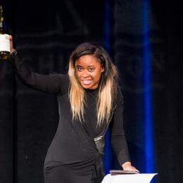Photo of comedian Phoebe Johnson leading a toast at the 2016 ACLU of Washington Bill of Rights Dinner